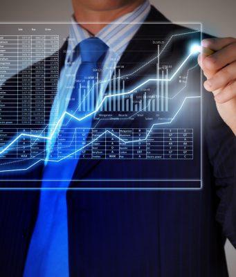 Hombre trajeado con gráfico de venta en una pantalla