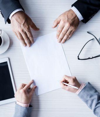 Detalle de persona firmando un papel y la otra persona enfrente
