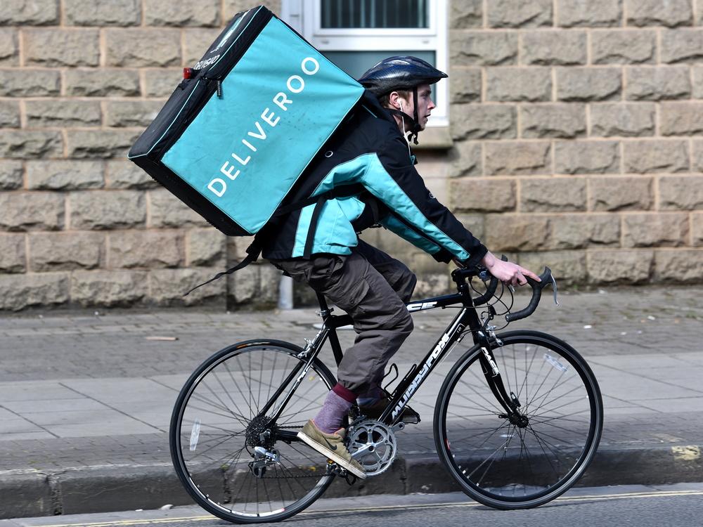 Trabajador servico comida a domicilio Deliveroo reparto en bicicleta